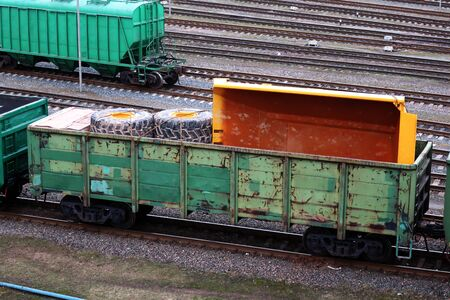 yellow truck body and wheels of a large truck transported in a railway wagon