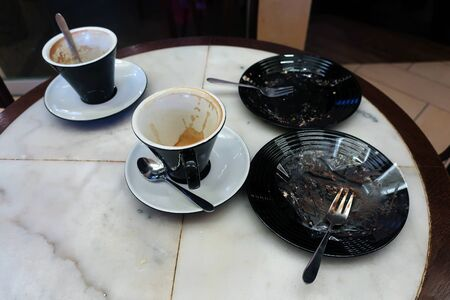 two cups and two saucers left on a table in a cafe after dessert