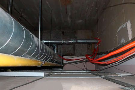 metal and corrugated pipes and communications, in the space above the false ceiling Foto de archivo