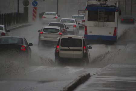 cars driving in heavy rain on a road sprinkling puddles in all directions