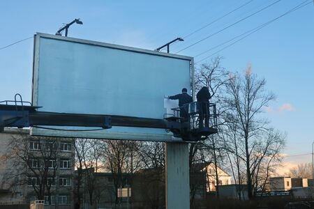 two workers on a hydraulic lift platform stick a poster on a billboard