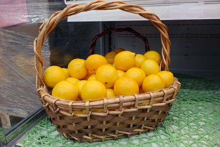 ripe juicy yellow lemons in a wicker basket on a shelf in the store