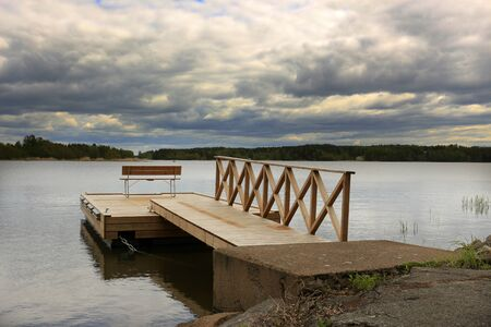 wooden pier with a railing and a bench for relaxing on the lake under a cloudy sky
