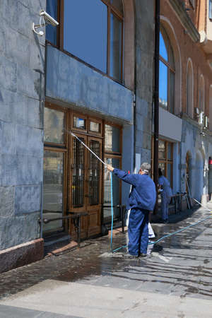 Cleaning company workers wash windows of a building with water from a hose