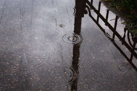 raindrops in a puddle on the pavement, which reflects the fence and pillar Banque d'images