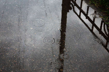circles on the water from raindrops in a puddle on the asphalt, which reflects the fence and post