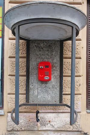 red push-button street telephone under a canopy with a handset hanging on a cord