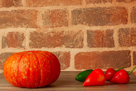 new crop of vegetables: pumpkin and peppers on a table against a brick wall