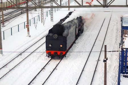 retro steam locomotive with one burning headlight rides on the railroad in winter 免版税图像