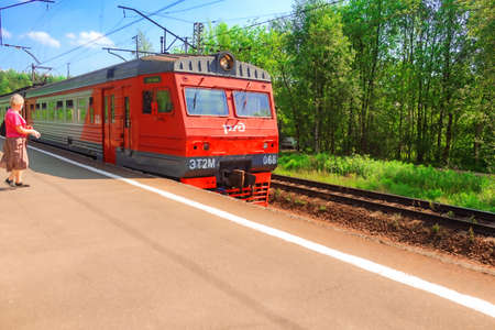 June 18, 2020, Russia, St. Petersburg, a suburban electric train approaches the platform, a woman in a mask and gloves is walking towards it