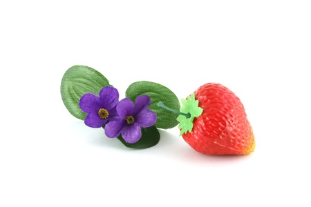 Artificial strawberries and violet flowers over white. Stock Photo - 8370798