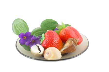 Artificial flowers, strawberries and sea shells on saucer. Stock Photo - 8584582