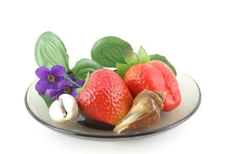 Artificial flowers, strawberries and sea shells on saucer. Stock Photo - 8629344