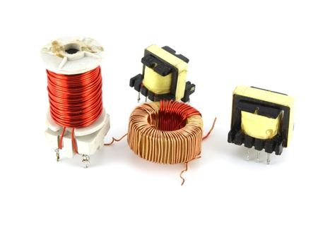 Old electronic transformers over white photo
