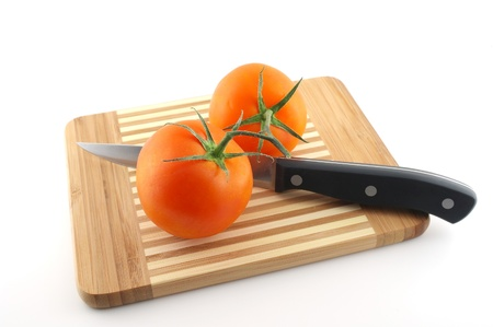 Kitchen-knife and red tomatoes on the preparation board photo