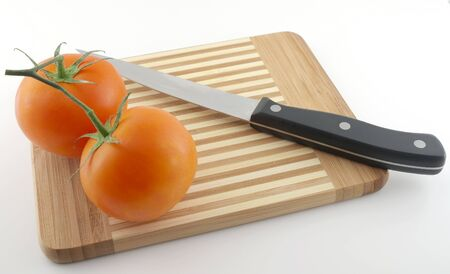 Kitchen-knife and red tomatoes on the preparation board Stock Photo - 11873755