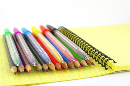 Color pen and pencils on the yellow writing-book. Shallow DOF. photo
