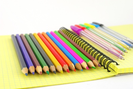 Color pen and pencils on the yellow writing-book. Shallow DOF. Stock Photo - 12085660