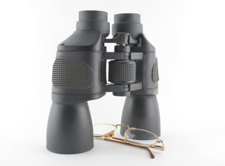 Binoculars and eyeglasses over white  photo