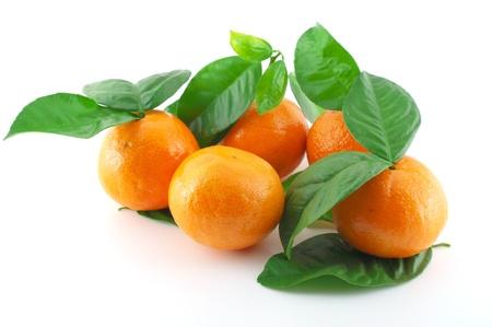 Ripe fresh mandarines with green leaves over white