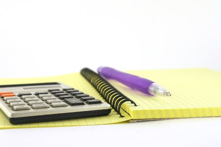 Calculator and pen on the yellow writing-book. Shallow DOF. photo