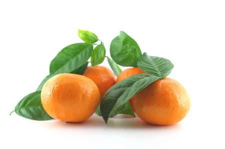 Ripe fresh mandarines with green leaves over white photo