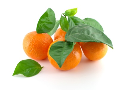 Ripe fresh mandarines with green leaves over white. Shallow DOF. photo