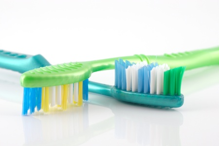 Two tooth-brushes over white photo