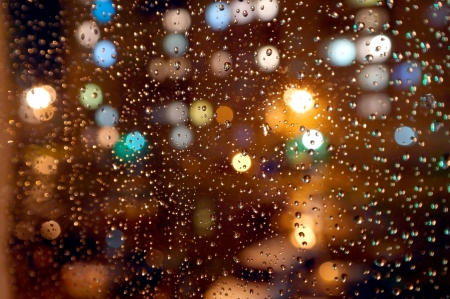 Drops of night rain on window, on back plan washed away lights of the torches. Shallow DOF