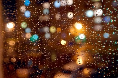 Druppels van de nacht regen op het venster, op de rug van plannen weggespoeld lichten van de fakkels. Ondiepe DOF Stockfoto
