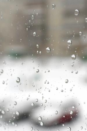 Op een winterse dag regent. Druppels water op het venster. Ondiepe DOF