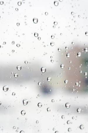 Op een winterse dag regent Druppels water op het venster Ondiepe DOF