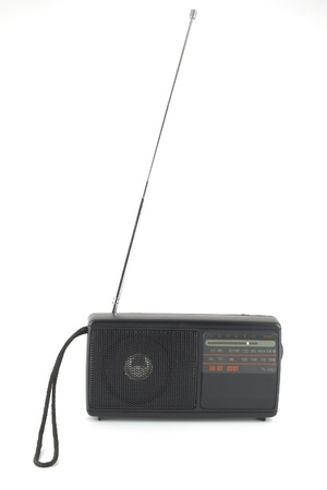 Old pocket radio with antenna over white photo