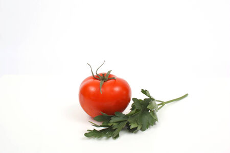 Tomato with parsley over white photo