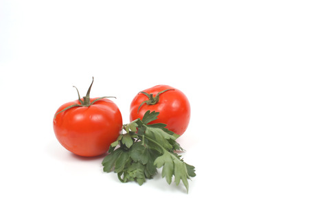 Tomatoes with parsley over white photo