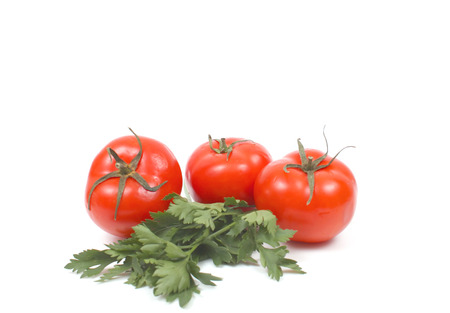 Tomatoes with parsley over white. Stock Photo