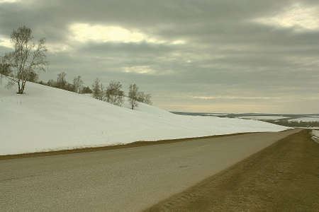 Spring countryside road and land with snow. Stock Photo