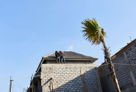 Workers put the roof shingles. Builders in the tropics