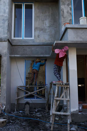 Two women make home repairs outside Zdjęcie Seryjne