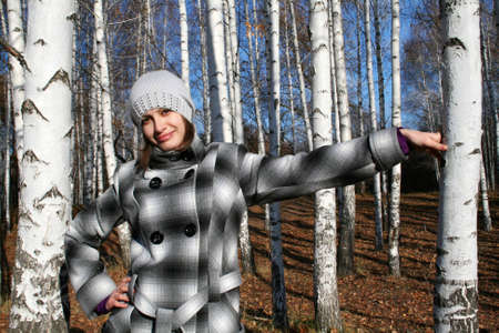 leant: The young beautiful girl in a checkered coat has leant about a birch