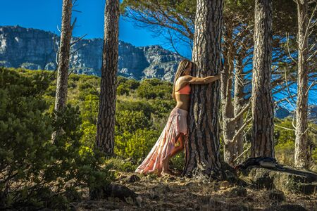 Beautiful woman hugging a tree in a forest with trees in the background.