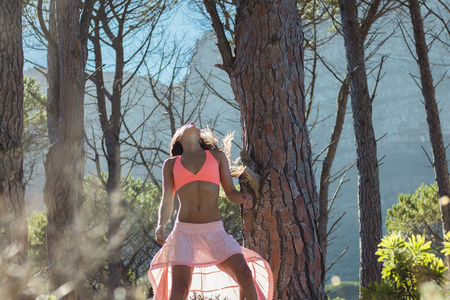 Beautiful woman dancing in a forest flicking her hair with trees in the background.