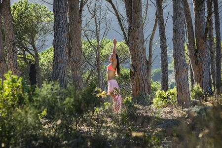 Beautiful woman doing yoga in a forest with trees in the background.