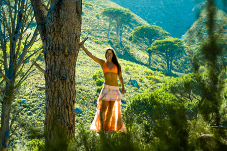 Beautiful woman standing next to a tree in a forest with mountain in the background.
