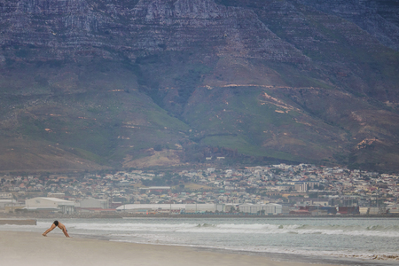 Man exercising on Paarden Eiland beach at sunrise with Table Mountain and Cape Town City in the background.