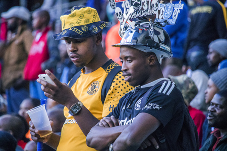 CAPE TOWN, SOUTH AFRICA, 12 May 2018 - Diverse South African football supporters checking score on their phone during PSL football match between Ajax Cape Town and Kaiser Chiefs.