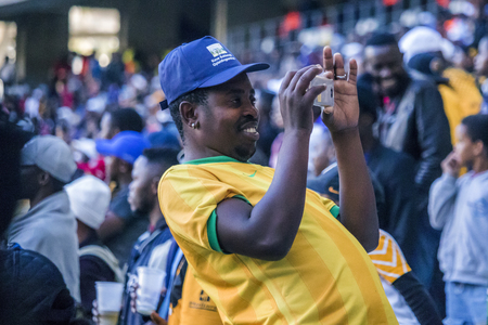 CAPE TOWN, SOUTH AFRICA, 12 May 2018 - Diverse South African football supporter taking a photograph during PSL football match between Ajax Cape Town and Kaiser Chiefs. Editorial