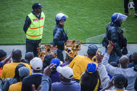 CAPE TOWN, SOUTH AFRICA, 12 May 2018 - Diverse South African football supporters cheering and celebrating and security guard lady smiles during PSL football match between Ajax Cape Town and Kaiser Chiefs.