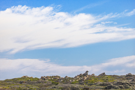 Rocks and wild grass on a hill with blue skies. Stock Photo
