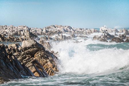 Dramatic crashing wave hitting rocks on the shore. Stock Photo